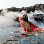 【画像】溶岩が流れ込む海岸でサーフィンを楽しむ女性が凄い!!